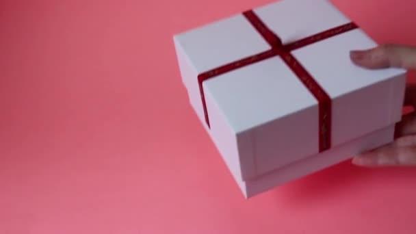 díszdobozban rózsával. Fehér ajándékdoboz rózsaszín háttérrel