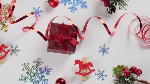 Flatley Christmas. Slavnostní vánoční pozadí. Nový rok a Vánoce. Pozadí vánočního přání. Červený dárek a sněhové vločky na bílém pozadí.