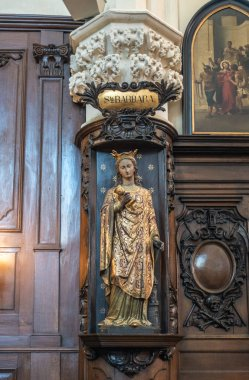 Brussels, Belgium - September 26, 2018: Inside Saint Nicolas Church. Santa Barbara statue with golden dress against dark wooden sculpted panels. Paining of arrest of Jesus.