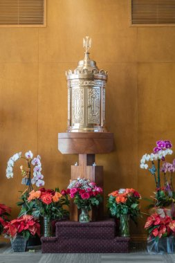 Garden Grove, California, USA - December 13, 2018: Crystal Christ Cathedral. Golden tabernacle in Blessed Sacramet Chapel against brown wooden wall. Many flowers up front.