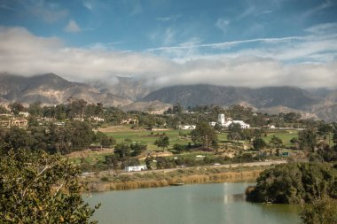 Santa Barbara, California, USA - December 18, 2018: Green golf course and white towered building of Montecito Country Club. Mountains partly shrouded in clouds under blue sky in back. Bird Refuge waters in front.