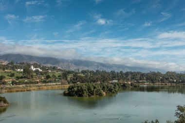 Santa Barbara, California, USA - December 18, 2018: Andreee Clark Bird Refuge lake and with Green golf course and white towered building of Montecito Country Club in back. Mountains partly shrouded in clouds under blue sky.
