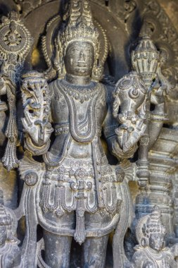 Belur, Karnataka, India - November 2, 2013: Chennakeshava Temple building. Closeup of Whitened Black stone well-preserved sculpture of Lord Vishnu or here called Kesava in full regalia.