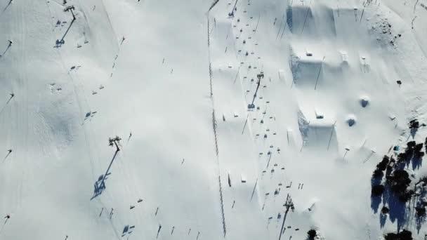Letecký pohled hladký pohyb podél sjezdovek v lyžařském středisku Grandvalira v Andoře. Lyžařské vleky s lyžaři. Nádherné zasněžené hory a modrá obloha. Zimní krajina. Zobrazení shora dolů.