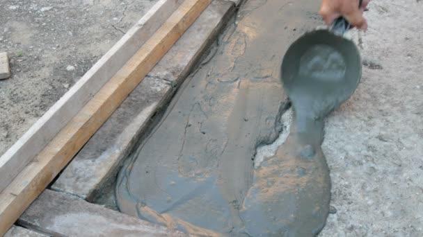 Dělník, rozprostření Malty nebo lepidla na dlaždice k betonu pomocí stěrky nástroje