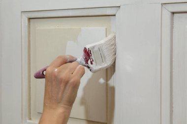 Painting of wooden door, workers hand and brush