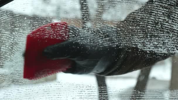 Řidič, úklid sněhu z čelního skla automobilu pomocí škrabky, detailní ledové ruce a nástroje