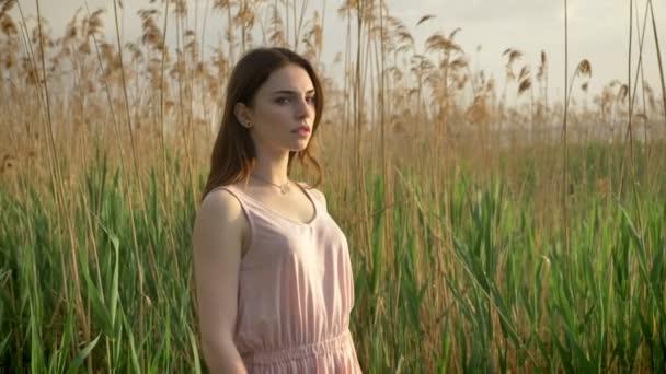 Mladý zázvor seriózní dívka v šatech stojí v lese, v přírodě, rostliny v pozadí 50 fps