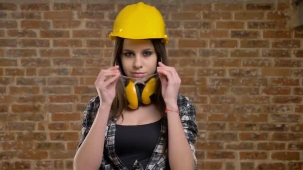 Mladé krásné atraktivní ženy v helmě dívá přímo do kamery a nasadil brýle, ženské tvůrce, cihlové pozadí