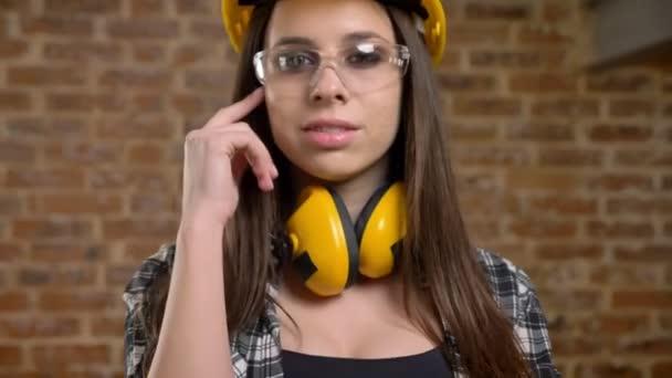 Mladé ženy docela atraktivní přilba, sluchátka a brýle dívá přímo do kamery a dotýká její dlouhé vlasy, Žena tvůrce, cihlové pozadí, closeup