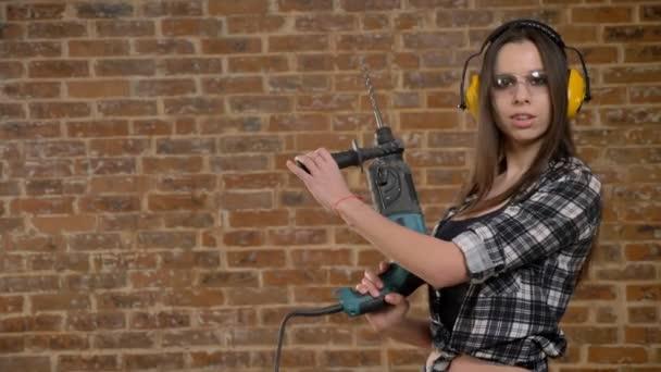 Nádherný atraktivní mladé ženy v brýle a sluchátka drží nástroje perforator a pohledu do kamery, ženské tvůrce, cihlové pozadí