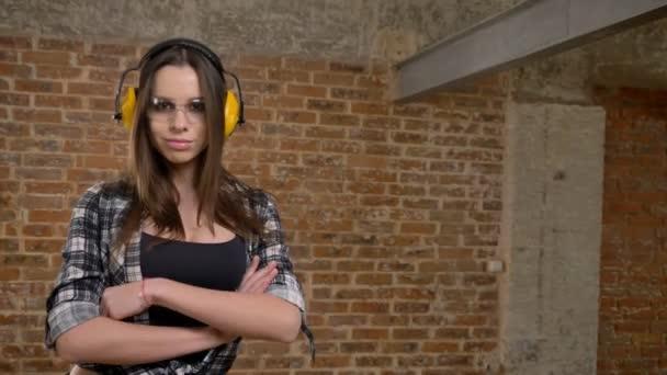 Nádherný atraktivní mladé ženy v brýle a sluchátka dokonale pohledu do kamery, křížení rukou a dojemné brýle, ženské tvůrce, cihlové pozadí
