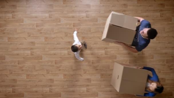 Mladá rodina přichází do prázdného domu s krabicemi, objímání, top shot parketové dřevěné podlahy