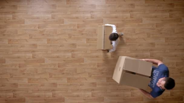 Mladý otec a syn do prázdného domu s boxy, nejlépe střílel, malý chlapec běží a objímání, otec, syn otce spinningu, parketové dřevěné podlahy