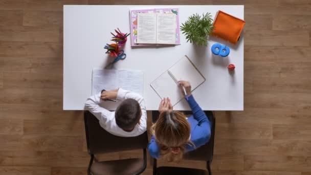Fiatal anya segít fia-tanulmány, táblázat, gyerek írt házi feladatot top shot fa parketta mögött ülve