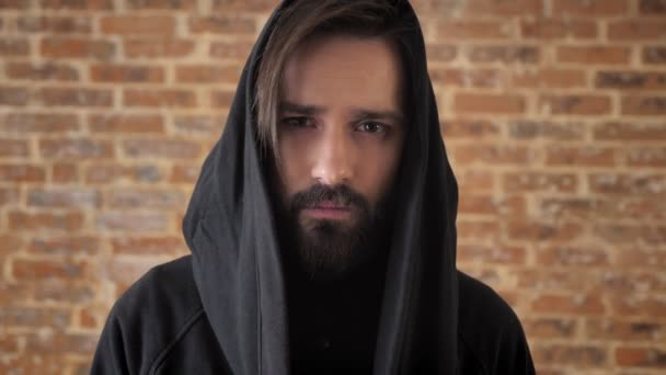 Young sad man with beard in hood is watching at camera, emotional concept, brick background