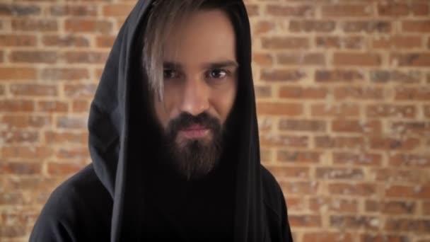 Mladý šílený muž s bradkou v kápi se dívá na fotoaparát, emocionální koncept, cihlové pozadí