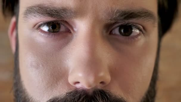 Eyes of young serious man with mustache, sadness, watching at camera.