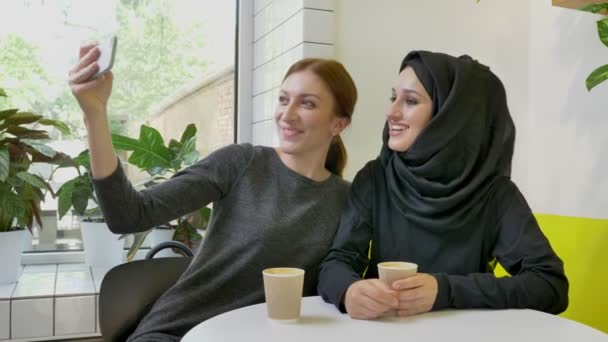 Two young charming womans sitting in cafe, one of them muslim woman in hijab, taking selfie with phone and posing, smiling