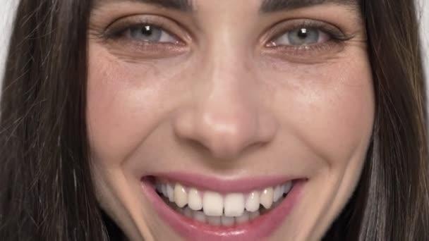 Portrét mladé okouzlující žena s modrýma očima, dívá přímo do kamery a smích, radost, bílé pozadí