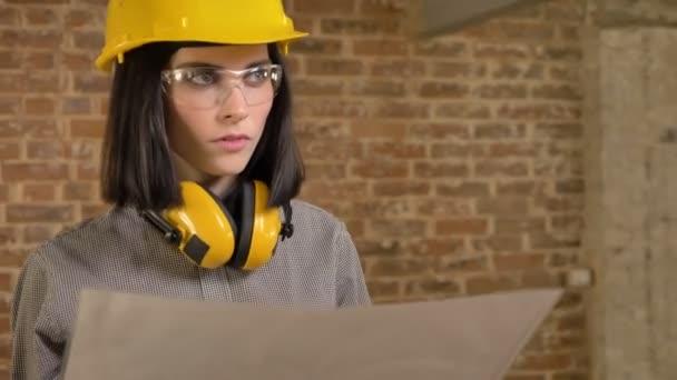 junge hübsche Architektin plant Neubau, blickt nach vorn und lächelt, konzentriert, Backsteinhintergrund