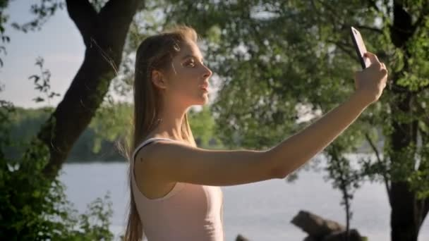 Young pretty woman with long hair taking selfie with her phone and smiling, park near river background, beautiful view