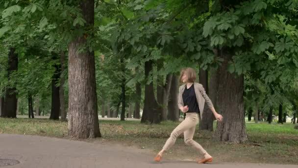 junge hübsche Tänzerin tanzt tagsüber im Park, im Sommer, Bewegungskonzept, Seitenansicht, Dolly Shot