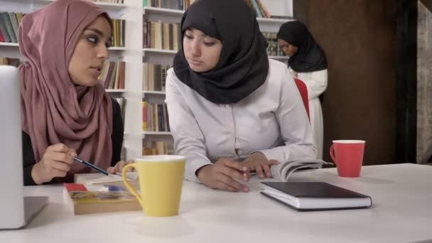 Mladí muslimské studentky v hidžábu studovat v knihovně, příprava na zkoušky, islámské studenty učení a mluvení