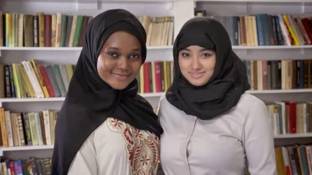 Porträt zweier hübscher junger muslimischer Frauen, die in der Bibliothek stehen und in die Kamera lächeln, islamische Freunde