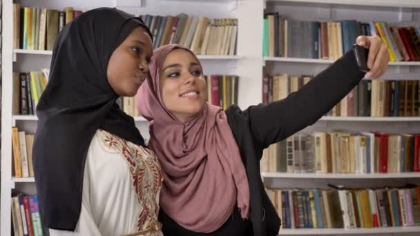 Young african muslim women in hijab with white friend taking selfie in library, then looking at phone, smiling and happy, islamic students