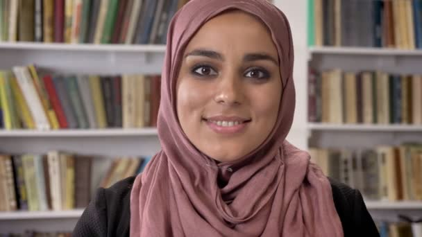 Portrait of young beautiful muslim women in hijab looking in camera and smiling, standing in library