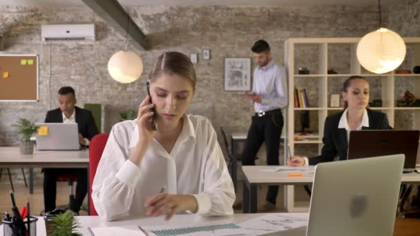 Mladá podnikatelka vážné mluví na telefonu v kanceláři, sledování dokumentů, lidé jsou sítě s technologií, pracovní koncept, obchodní koncept, komunikační koncept