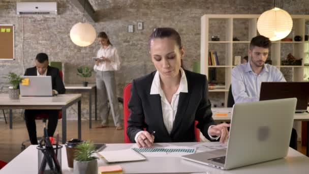 Young serious businesswoman is watching laptop and graphics in office, people are networking with technologies, working concept, business concept, communication concept