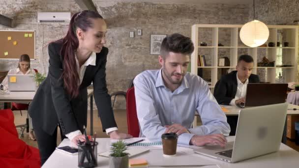 Dva mladí podnikatelé mluví, sledování grafiky a přenosný počítač v kanceláři, síťové technologie, pracovní koncept, obchodní koncept, komunikační koncept