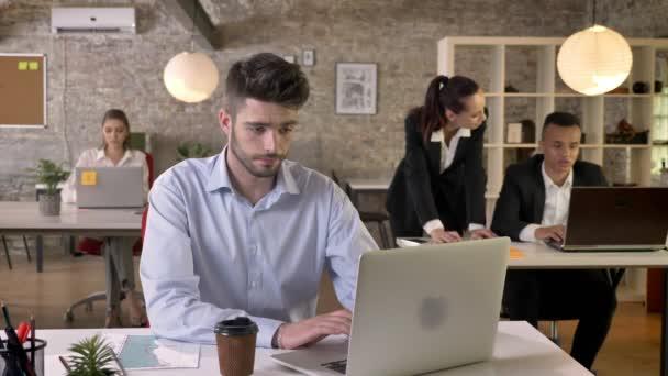 Mladý podnikatel unavený pracuje v kanceláři, na notebooku, diskuse o pozadí, pracovní koncepce, koncepce, komunikační koncept