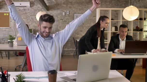 Mladý podnikatel má radost z úspěchu v úřadu, kolegové jsou pogratuloval mu pracovní koncept, obchodní koncept, komunikační koncept