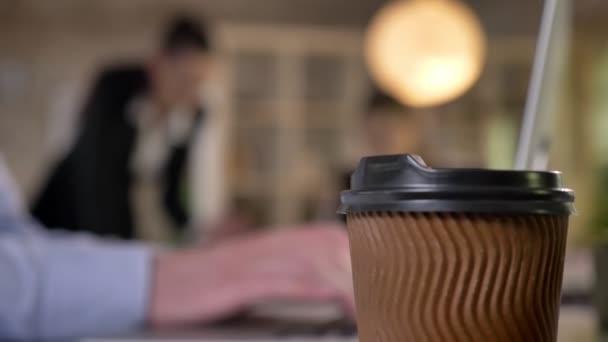 Šálek kávy na stole v kanceláři, rukou podnikatelů jsou psaní na notebooku, jeho kolegové jsou diskuse o práci, rozmazané pozadí, pracovní koncept