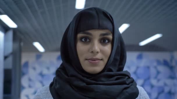 Young charming muslim woman in hijab is standing in underpass, watching at camera, religion concept