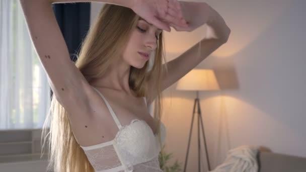 Mladá blond ženy spráskla ruce a postavení v moderní světlé místnosti, portrét krása