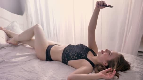 Fiatal szexi lány szóló fehérnemű ágyon, így selfie a smartphone, mosolyogva, bolondozás körül, kommunikáció fogalma