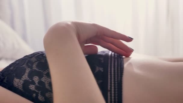Young sexy girl is laying in lingerie on bed and touching her body, flirt concept