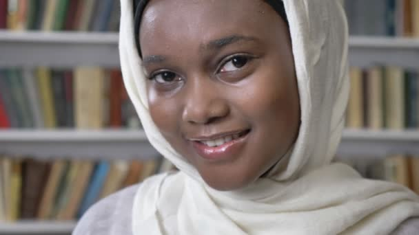 Face of young charming african muslim girl in hijab is watching at camera, religioun concept, booksheves on background