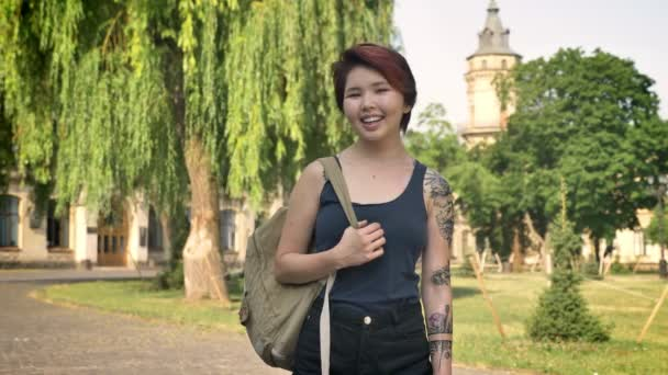 Young asian women with tattoo standing and looking in camera near university in park, student holding backpack, smiling