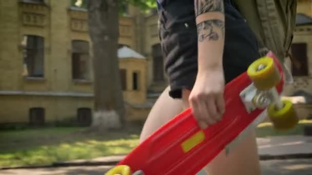 Extraordinary young women with tattooed hand walking away from university and holding skateboard