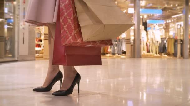 Nohy mladá dívka jde nakupovat v obchoďáku, dívá se na showcase, drží tašky, nákupní koncept módní koncept