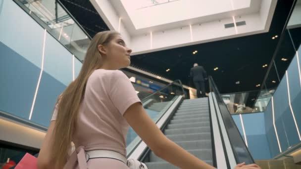 Mladá atraktivní dívky stojící na eskalátor v obchodním domě, hospodářství tašky, nákupní koncept, módní pojem