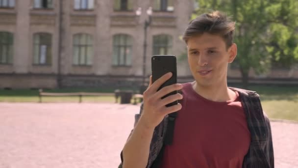 Young handsome man has call in videochat on smartphone in park in daytime in summer, communication concept