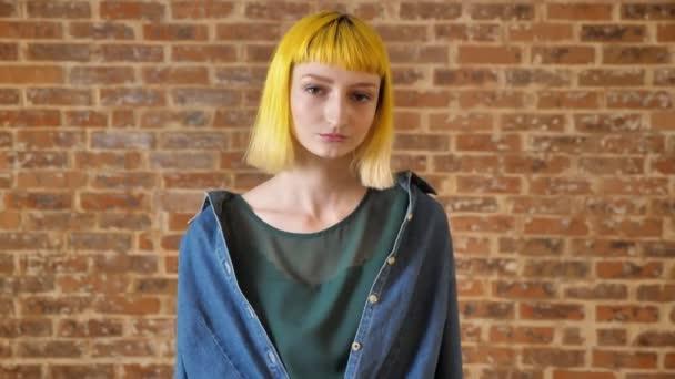 Mladá krásná žena se zlatými vlasy, při pohledu na fotoaparát a stojící poblíž cihlová zeď na pozadí, neobvyklí lidé