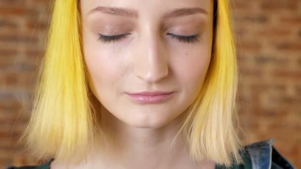 Portrét mladé ženy s vlasy otevírá oči, cihlová zeď na pozadí, model s neobvyklý účes se zavřenýma očima