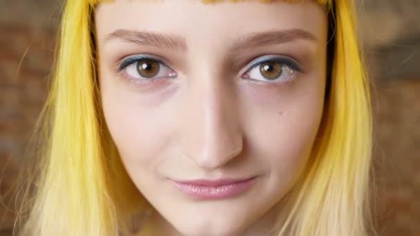 Úzké portrét tváře Zenske se zlatými vlasy, při pohledu na fotoaparát a usměvavý, neobvyklý účes